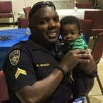 A photo provided by Trenisha Jackson shows her husband, Montrell Jackson, holding his son, Mason, at a Father's Day event for police officers in Baton Rouge, La. Montrell Jackson and two other law enforcement officers were killed Sunday.