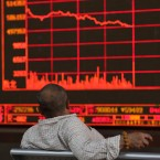 A Chinese investor watches as the Shanghai Composite Index falls at a brokerage In Beijing on Monday, May 6, 2019. China's benchmark Shanghai Composite index dives on Trump threat of more China tariffs.