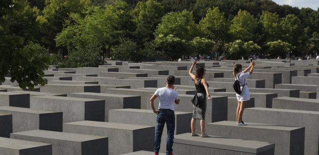 Visitors photograph each other while standing on concrete slabs at the Holocaust Memorial in Berlin