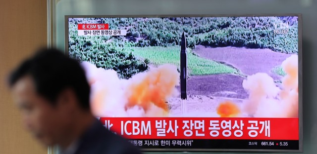 "A man walks by a TV screen showing a local news program reporting about North Korea's missile firing at Seoul Train Station in Seoul, South Korea, Wednesday, July 5, 2017. North Korea's leader Kim Jong Un vowed his nation would ""demonstrate its mettle to the U.S."" and never put its weapons programs up for negotiations a day after test-launching its first intercontinental ballistic missile. The hard line suggests more tests are being prepared as the country tries to perfect a nuclear missile capable of striking anywhere in the United States. The letters read ""North Korea, release an ICBM launching video."""
