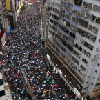 Demonstrators carry umbrellas as they march along a street in Hong Kong, Sunday, Aug. 18, 2019. Heavy rain fell on tens of thousands of umbrella-ready protesters Sunday as they started marching from a packed park in central Hong Kong, where mass pro-democracy demonstrations have become a regular weekend activity.