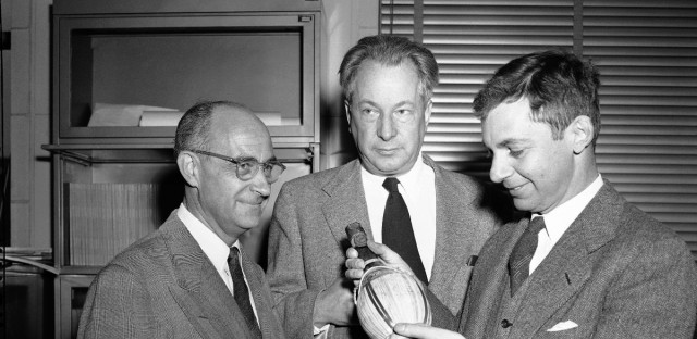 A decade of the atomic age is commemorated by scientists, from left, Enrico Fermi, Samuel K. Allison and Herbert L. Anderson, as they hold the empty wine bottle from which toast were made, Dec. 2, 1942, at the University of Chicago squash court.