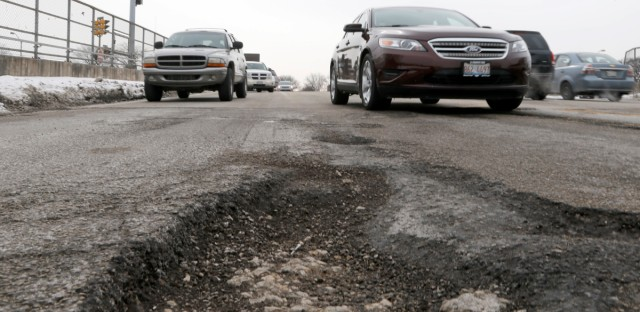 Motorists traveling on Chicago's Austin Ave. dodge potholes and pass a hubcap as the effects of a harsh winter continue to challenge the city's infrastructure on Feb. 12, 2014.