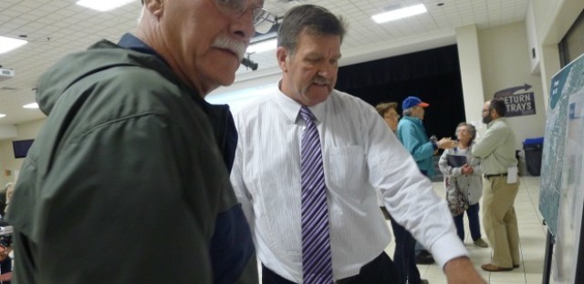 Lowell, Indiana resident Gary Kistler (left) goes over a map with an Indiana transportation official showing where the Illiana Tollway will go. Kistler opposes the building of the Illiana Tollway.