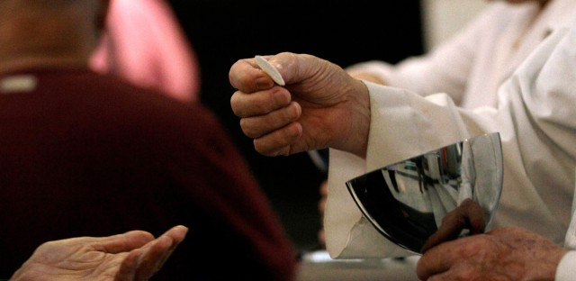 In this May 29, 2013 photo, a Eucharistic Minister serves communion during Mass at a Catholic church in Caracas, Venezuela. Church officials say food shortages and foreign exchange restrictions are causing a lack of ingredients needed to celebrate Mass: altar wine as well as wheat to produce communion wafers.