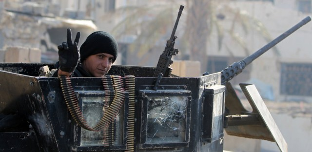 "A member of Iraq's elite counter-terrorism service flashes the ""V"" for victory sign Tuesday in Ramadi, the capital of Iraq's Anbar province. Iraq's prime minister says the extremist group will be pushed out of Iraq in 2016."