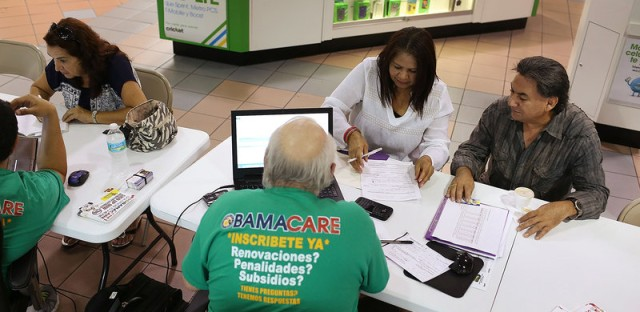 From left: Martha Lucia Bienvendida Barreno and Jorge Baquero discuss health insurance options with agents from Sunshine Life and Health Advisors at a Miami mall last month.
