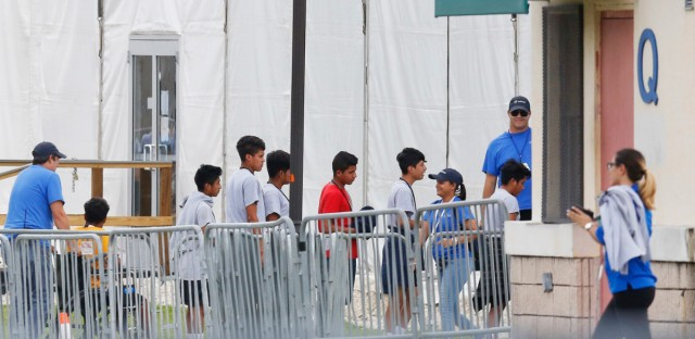 Immigrant children walk in a line outside the Homestead Temporary Shelter for Unaccompanied Children a former Job Corps site that now houses them in Homestead, Fla. on June 20.
