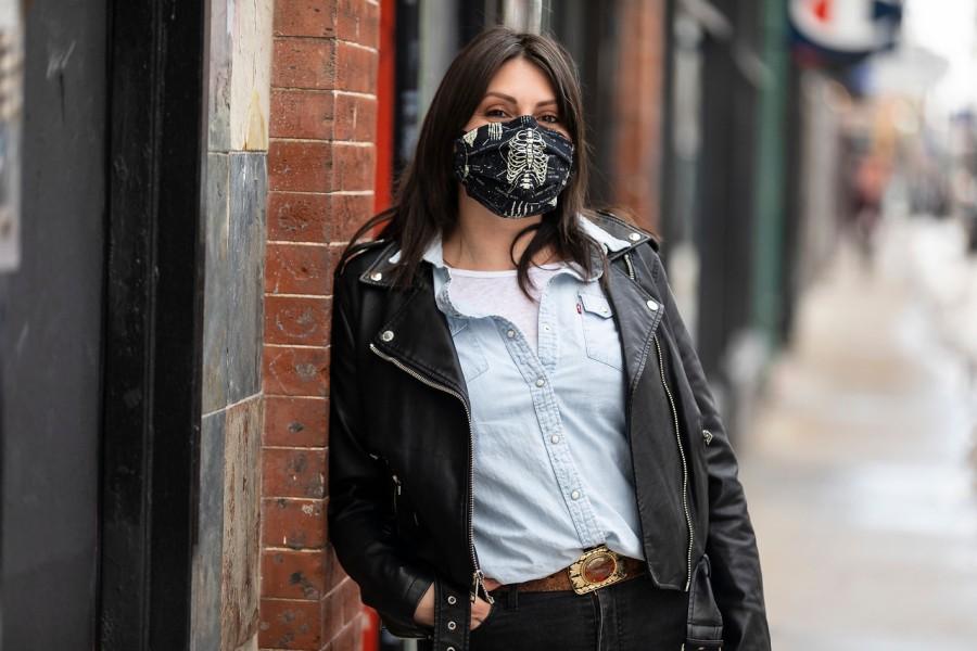 Restaurant worker Allison June Palmer, wearing a black mask, stands on a sidewalk.
