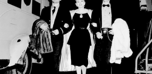"""Traveling with three fur coats and a $950,000 diamond known as the """"Shah of Persia,"""" Gabor is escorted by two Brinks guards as she arrives at CBS's Television City in Hollywood on Dec. 1, 1955."""