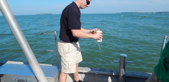 Justin Chaffin is a researcher at OSU's Stone Lab on Gibraltar Island in Lake Erie. He drops a device down into the lake to measure oxygen and retrieve water to test for algae.