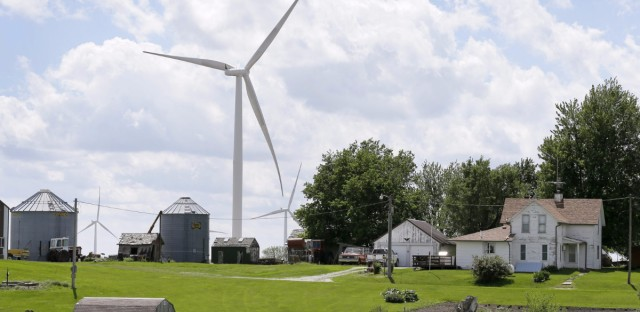 A wind turbine stands over a farmhouse in Adair, Iowa.