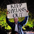 "A counterdemonstrator holds a sign during a gathering in New York City to show solidarity with Syrian and Iraqi refugees last year. Donald Trump's hard-line campaign rhetoric singled out Syrian refugees. ""If I win,"" he told a New Hampshire rally, ""they are going back."""