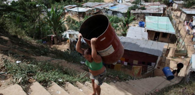 A woman carries an empty barrel to collect fresh water in Filas de Mariches neighborhood in Caracas.