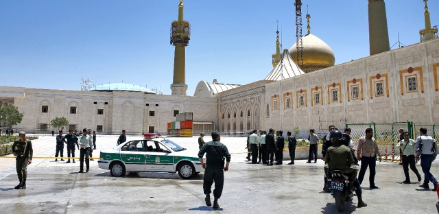 Police officers control the scene, around of shrine of late Iranian revolutionary founder Ayatollah Khomeini, after an assault by several attackers in Tehran, just outside Tehran, Iran, Wednesday, June 7, 2017. Suicide bombers and gunmen stormed into Iran's parliament and targeted the shrine of Ayatollah Ruhollah Khomeini on Wednesday, killing a security guard and wounding several other people in rare twin attacks, with the siege at the legislature still underway.