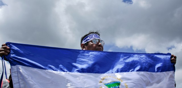 A man holds a Nicaraguan national flag during a demonstration supporting journalists recently attacked while covering protests demanding the resignation of President Daniel Ortega and the release of all political prisoners, in Managua, Nicaragua, Monday, July 30, 2018