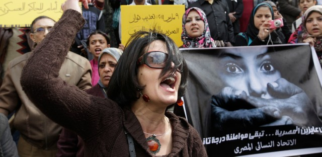 "In this Friday, March 16, 2012 file photo, an Egyptian activist chants slogans during a demonstration against an army doctor accused of public obscenity filed by a protester who claimed she was forced to undergo a virginity test, in front of Cairo's high court, in Egypt. Women protesters and rights groups have accused Egyptian military and prison authorities of sexual assault and abuse on female detainees in the latest crackdown on demonstrations. Arabic on the poster, center, reads, ""March 9, 2011, protesters torture "" and the banner, left, reads, ""we do not want the Egyptian woman to be a second-class citizen."""