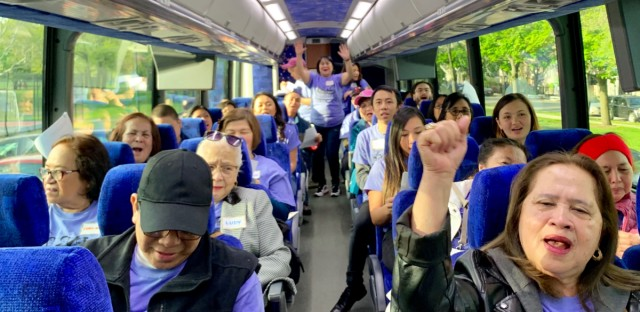 Members of the Alliance of Filipinos for Immigrant Rights and Empowerment (AFIRE) practice a chant on the bus before departing for the Asian American Action Day rally in Springfield on May 15, 2019.