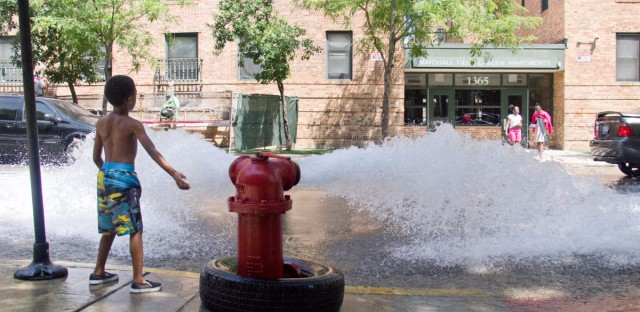 A child plays in an open fire hydrant outside the main entrance to Manierre Elementary on a summer day. The school's entrance is directly across from the Marshall Field complex of subsidized housing. The school's playground is behind the school and, according to Manierre's principal, students are discouraged from using it after school by security guards.