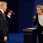 In this Sunday, Oct. 9, 2016, file photo, Republican presidential nominee Donald Trump and Democratic presidential nominee Hillary Clinton speak during the second presidential debate at Washington University in St. Louis. Trump gets outsized attention for what he's tweeting and retweeting on a near-daily basis. But Clinton has a formidable digital media army, her own app and a rapid response team ready to blast out shareable soundbites from convention speeches, photos, videos and even temporary location-specific Snapchat filters mocking Republicans.