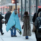 A homeless man who did not give his name bundles up in blankets Tuesday morning, Jan. 28, 2014, in downtown Chicago. The National Weather Service is reporting the air temperature dropped to 11 degrees below zero at O'Hare International Airport and Midway International Airports on Tuesday morning. Cold temperatures have forced the cancellation of about 625 flights at Chicago's major airports. (AP Photo/Kiichiro Sato