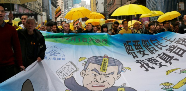 """Pro-democracy activists carry a banner depicting Hong Kong Chief Executive Leung Chun-ying during a march to Central, demanding for universal suffrage in Hong Kong Sunday, Feb. 1, 2015. The march is the first large-scale demonstration since the Occupy Central protest ended last year as the government started a second round of public consultation on democratic reform. The banner reads: """"No fake democracy, I want genuine universal suffrage."""