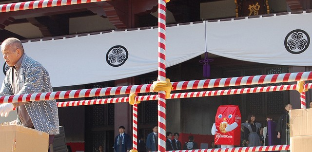 Tohato Caramel Corn mascot waits to throw lucky food at Zojoji temple in Tokyo, Japan on Setsubun
