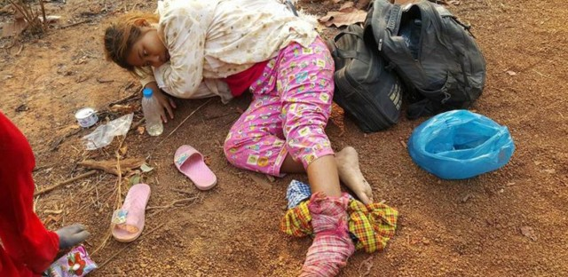 Phan Sopheak, a rice farmer in Cambodia, rests shortly after a man wielding an axe attacked her. She had been patrolling the Prey Lang forest around her village with a volunteer group that is trying to stop illegal logging.