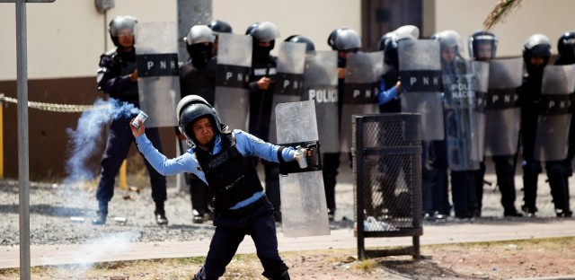 A police officer throws a tear gas at grenade at demonstrators during a protest against the government of Honduras' President Juan Orlando Hernandez, outside the campus of the National Autonomous University in Tegucigalpa, Honduras, Monday, Jan. 28, 2019. Hernandez was re-elected in a result marred by irregularities and denounced by his opponents as unconstitutional.