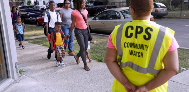 Safety guard Renee Green watches as parents walk with their children along a safe passage route on the first day of school in Chicago on Aug. 26, 2013.