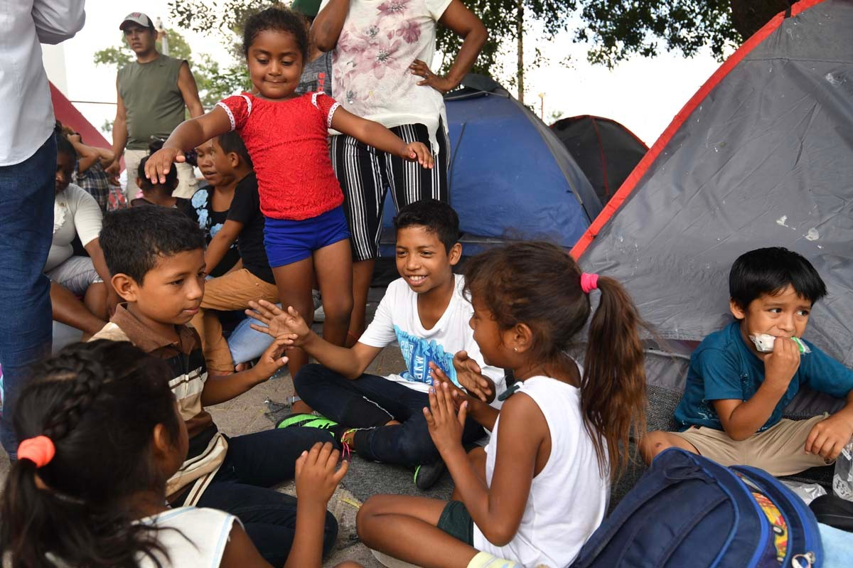 Children gather in front of tents in Matamoros, Mexico