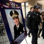 Chicago police officers pass a memorial portrait of Cmdr. Paul Bauer for a candlelight vigil for Bauer outside the Near North District headquarters Wednesday, Feb. 14, 2018, in Chicago. The 53-year-old Bauer, who had been with the department 31 years, was fatally shot as he went to assist other officers who were pursuing the suspect, Shomari Legghette, in downtown Chicago on Tuesday. Legghette is charged with first-degree murder in the shooting of Bauer.
