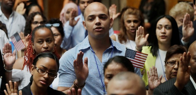 New citizens participate in a naturalization ceremony, Tuesday, July 3, 2018, at the New York Public Library. Two hundred people from 50 countries gained citizenship. (AP Photo/Mark Lennihan)