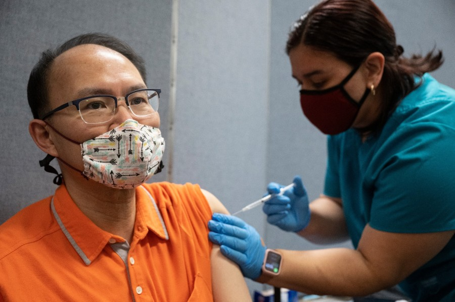 Man receives vaccination at Chinatown site