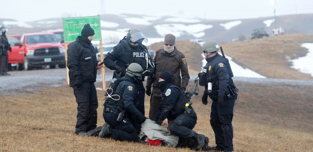 Police make arrests as they move south on highway 1806, just outside the entrance to the Oceti Sakowin camp on Wednesday.