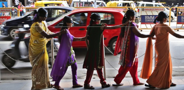 Blindfolded women walk in a row to join visually impaired people during a 'Blind Walk' in Bangalore, India, Sunday, Aug. 24, 2014. Some 600 people participated in the walk that was organized to create awareness about blindness and encourage people to donate their eyes, the organizers said.