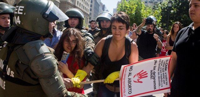 Pro and anti-abortion demonstrators clash, in front of a police officer in riot gear, during a pro-abortion protest in Santiago, Chile, Monday, March 21, 2016.