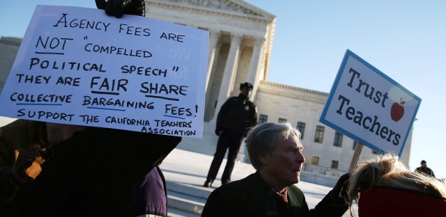 People for and against unions hold up signs Monday in front of the U.S. Supreme Court building in Washington. The court was hearing arguments in Friedrichs v. California Teachers Association. Justices will decide whether California and other states can make nonunion public employees covered by union contracts pay partial dues.