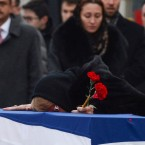 Marina Karlov, the wife of slain Russian Ambassador to Turkey Andrei Karlov, lays her head on his coffin during a ceremony at Esenboga International Airport on Tuesday in Ankara, Turkey.