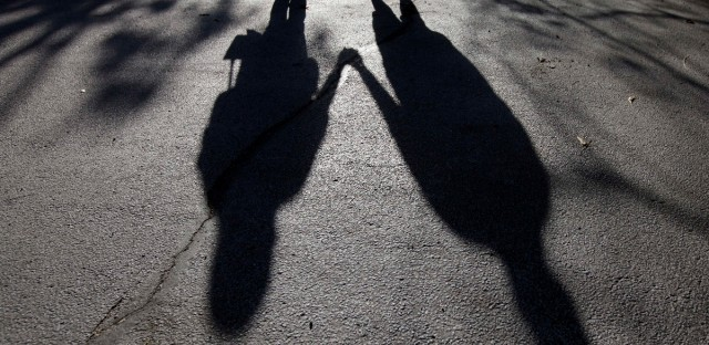 "This Sept. 20, 2012 photo shows the shadows of a young woman from Rockford, Ill., left, with her husband. When her doctor said a medical condition made her unplanned pregnancy too risky, she decided to go ahead with an abortion in 2011. Abortion protesters were picketing outside when the young couple arrived in the parking lot for the procedure. One protester was particularly persistent. ""She was just blatantly yelling at my fiance and I. I turned around and said, 'Listen, lady, you don't know what everyone is going through.' She was just saying that I was already a mom and I have all these options - the opposite of what my doctor was telling me. ""I looked at her and told her, 'I'm doing this to save my life.'"" (AP Photo/Nam Y. Huh)"
