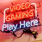 "A neon sign that reads ""Video Gaming Play Here"""