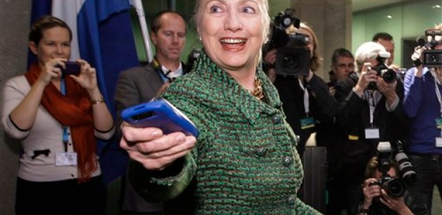 In this Dec. 8, 2011, file photo, then-U.S. Secretary of State Hillary Rodham Clinton hands off her mobile phone after arriving to meet with Dutch Foreign Minister Uri Rosenthal at the Ministry of Foreign Affairs in The Hague, Netherlands. Clinton emailed her staff on an iPad as well as a BlackBerry while secretary of state, despite her explanation that she exclusively used a personal email address on a homebrew server so she could carry a single device, according to documents obtained by The Associated Press.