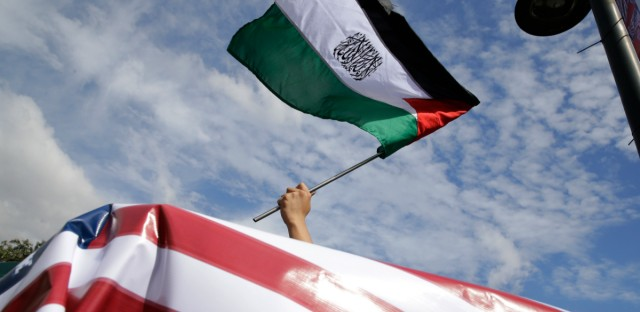 A Muslim protester waves a Palestinian flag as they tried to march towards the Israel embassy during a protest against U.S. President Donald Trump's decision to recognize Jerusalem as the capital of Israel in metropolitan Manila on Thursday Dec. 21, 2017. The protesters insist that Jerusalem is the capital of Palestine and demanded Trump to recall his statement.