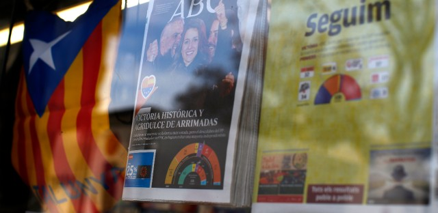 Newspapers are displayed featuring the results at the Catalan regional election next to an Estelada', the pro-independence Catalan flag, at a news stand in Barcelona, Spain, Friday, Dec. 22, 2017.