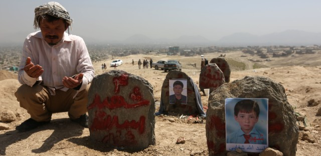 An Afghan man prays in front graves of victims of a suicide attack, in Kabul. Afghanistan held a national day of mourning on Sunday, a day after a suicide bomber killed at least 80 people who were taking part in a peaceful demonstration in Kabul. The attack was claimed by the Islamic State group.