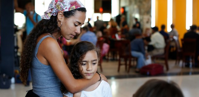 Andrea Cecilia, 16, and her sister Amidala Amira, 8, wait in the San Juan airport for their flight to Miami.