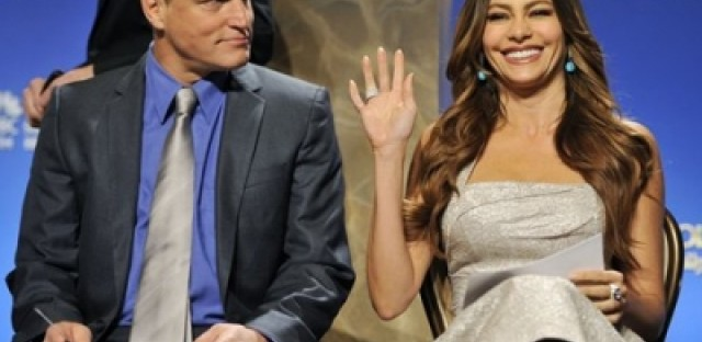Sofia Vergara waves to photographers as Woody Harrelson looks on before they announced the 2011 Golden Globe nominees.