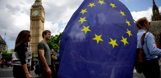 A remain supporter stops to talk to people as he walks around with his European flag across the street from the Houses of Parliament in London.