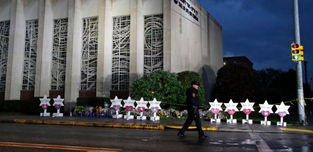 In this Oct. 28, 2018, file photo a Pittsburgh Police officer walks past the Tree of Life Synagogue and a memorial of flowers and stars in Pittsburgh in remembrance of those killed and injured when a shooter opened fire during services Saturday at the synagogue. The social media site popular with far-right extremists and apparently used by the Pittsburgh synagogue shooting suspect, advertises as a haven for free-speech fans. As more mainstream sites have cracked down on hate speech and threats of violence, critics say Gab has become a breeding ground for white nationalists, neo-Nazis and other extremists.