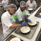 Employees hand-finish cheesecakes on the production line at Eli's in Chicago.
